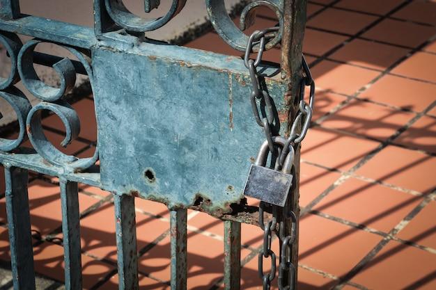 Vecchio lucchetto in acciaio appeso alla catena al recinto di metallo arrugginito
