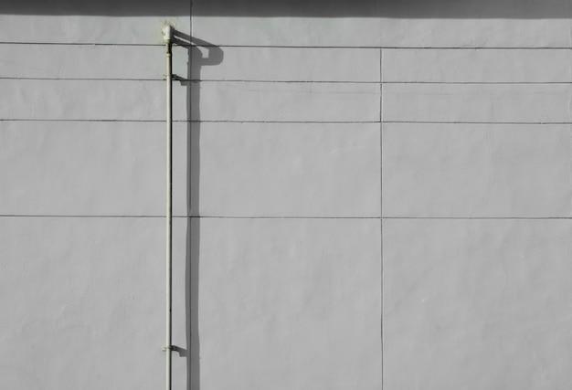 Vecchio tubo d'acciaio con ombra al muro di cemento grigio.
