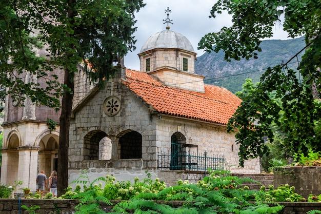 Vecchia chiesa in pietra con tetto di tegole rosse vicino