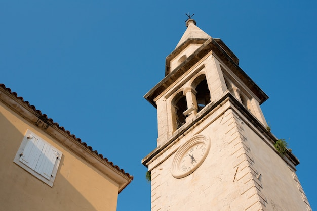 Vecchia chiesa medievale in pietra con orologio