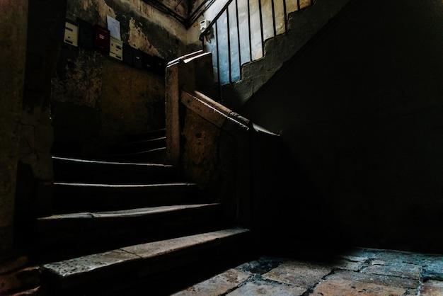 Vecchie scale di pietra nell'atrio buio di un edificio in disuso nella parte vecchia di bari, italia.