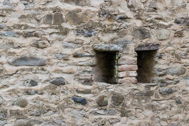 Vecchio muro di pietra del primo piano del castello o della fortezza