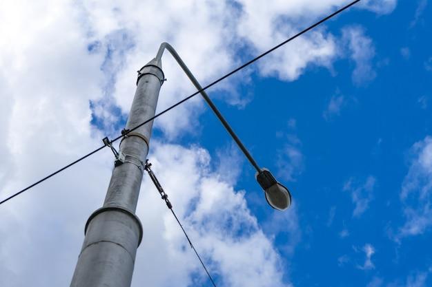 Vecchio lampione con molti cavi collegati, isolato su cielo grigio. copia spazio.