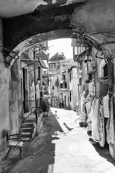 Vecchia strada con case diroccate a catania, sicilia, italia. immagine in bianco e nero