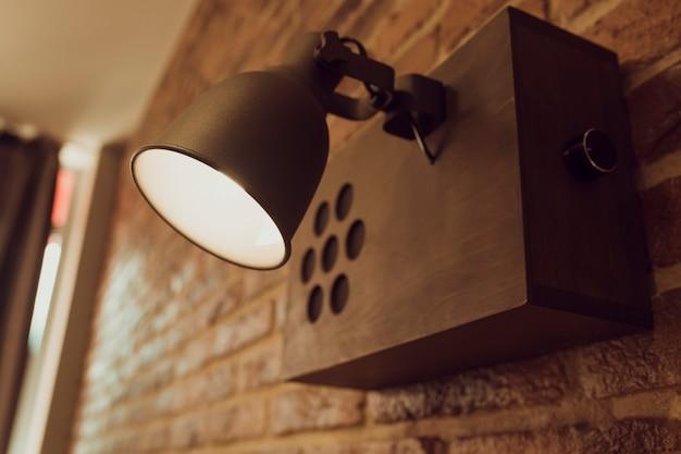 Lampada in vecchio stile appesa a un muro di mattoni. primo piano