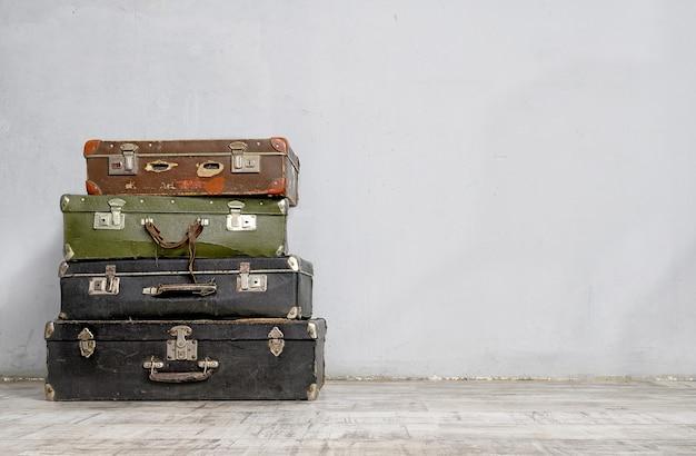Vecchie valigie impilate vicino al muro di cemento bianco in una stanza vuota. concetto di bagaglio in stile retrò con spazio di copia.