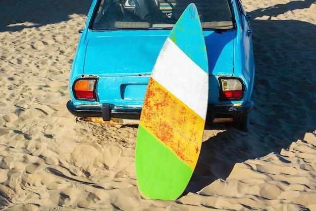Vecchia tavola da surf su auto arrugginita in riva al mare.