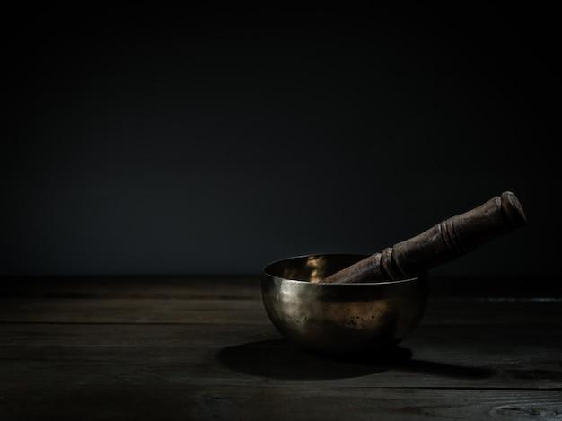 Vecchia ciotola tibetana di canto sulla base di legno, fondo nero. musico-terapia.