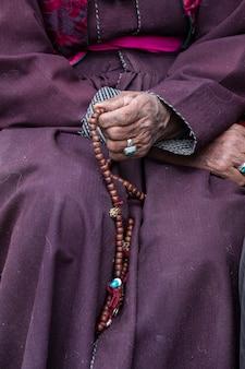 Vecchia donna tibetana azienda rosario buddista nel monastero di hemis, ladakh, india. mano e rosario