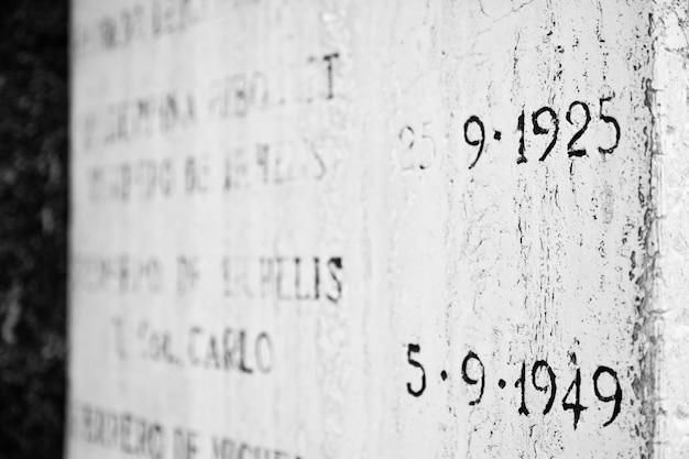 Vecchia lapide nel cimitero italiano con date di nascita e morte