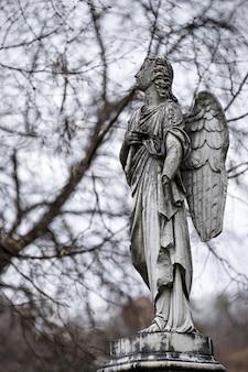 Vecchia scultura in pietra tombale di un angelo con braccio rotto e ali sul cimitero
