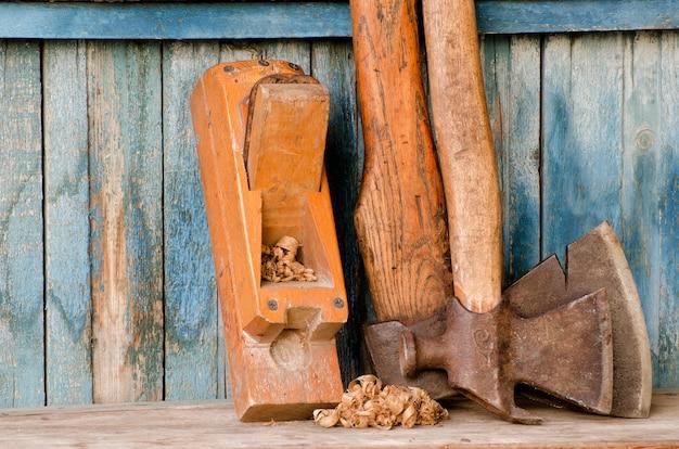 Vecchi strumenti. ascia e aereo su uno sfondo di legno d'epoca