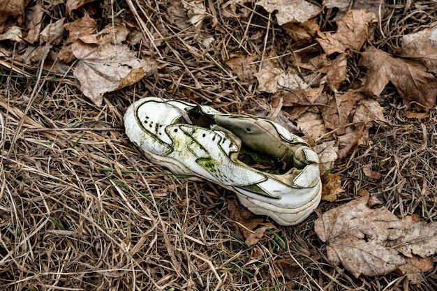 Vecchie scarpe da ginnastica strappate nell'erba sporca.