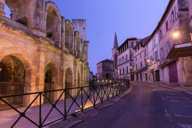 Città vecchia e anfiteatro romano di arles durante l'ora blu serale, arles, provenza, francia meridionale