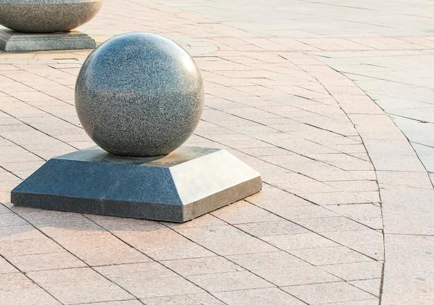 Vecchio fondo del mattone della strada della via della città e palla del granito.