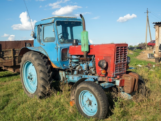 Vecchio trattore blu parcheggio i.in iackyard in summer sunny day