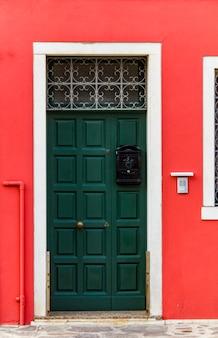 Vecchia porta tradizionale su costruzione variopinta all'isola di burano, italia