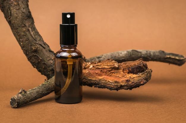 Un vecchio albero e una bottiglia di polverizzatore su uno sfondo marrone. cosmetici e medicinali a base di minerali naturali.
