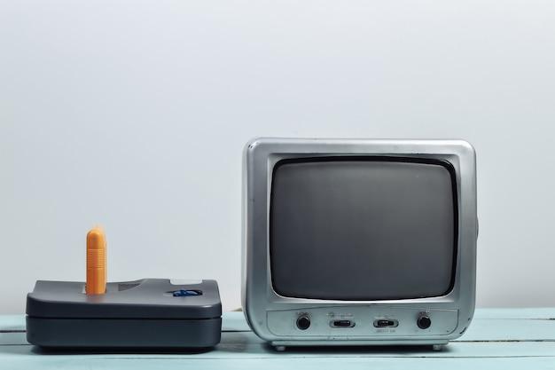 Vecchio ricevitore tv con console di gioco retrò sul muro bianco. giochi retrò