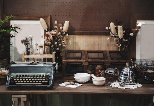 Vecchia macchina da scrivere e attrezzatura aromatica sul tavolo di legno in giardino interno con vecchio stile di moda