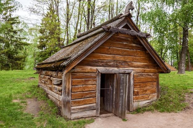 Vecchia casa ucraina con un tetto in legno e un'insolita porta d'ingresso