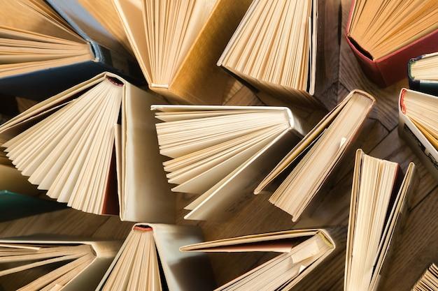 Libri con copertina rigida vecchi e usati, libri di testo visti dall'alto sul pavimento di legno.