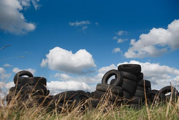 Vecchi pneumatici usati accatastati con pile alte
