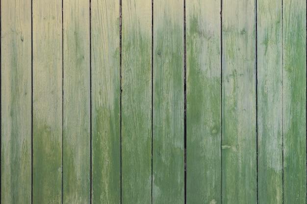 Vecchi bordi verticali chiazzati dipinti di pittura verde come fondo