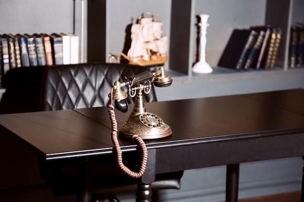 Vecchio telefono antico d'annata del candeliere sulla tavola di lavoro di affari che lavora al passato.