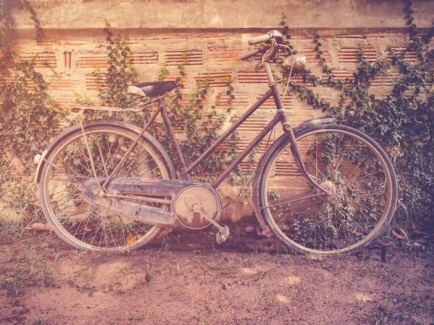 Vecchio parcheggio di bicicletta d'epoca a casa di parete grunge con filtro retrò.