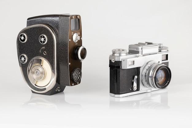 Vecchia macchina fotografica e videocamera a pellicola vintage su bianco isolato da vicino