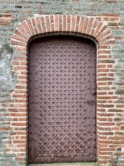 Vecchia porta d'annata del metallo sul muro di mattoni