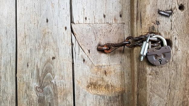 Vecchio lucchetto vintage in metallo su una porta di legno chiusa di una vecchia fattoria. il vero stile del villaggio. avvicinamento. concentrarsi sul castello. fondo in legno, trama. copia spazio.
