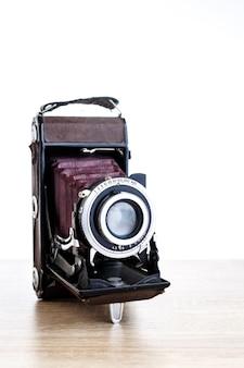 Vecchia macchina fotografica della foto dell'annata sul tavolo e bianco
