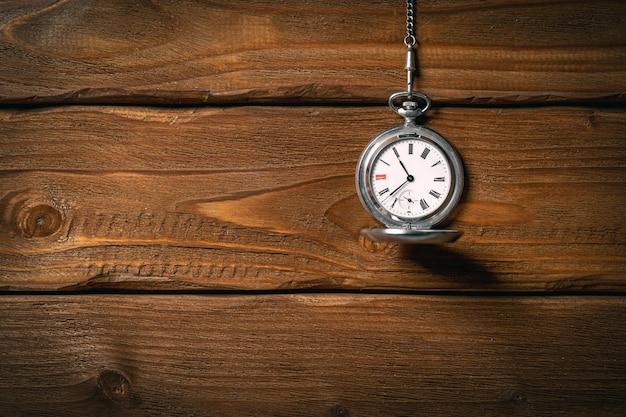 Vecchio orologio da tasca vintage sulla catena sul fondo della tavola in legno