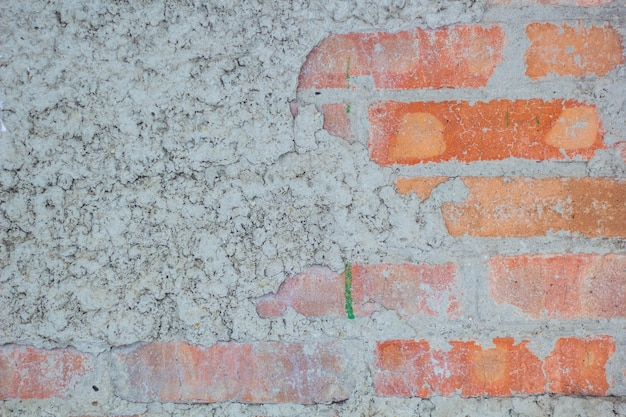 Vecchio muro di mattoni rossi dell'annata con fondo di struttura dell'intonaco bianco spruzzato