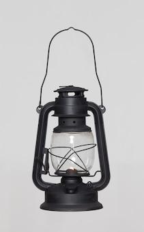 Vecchia lampada arrugginita nera del cherosene dell'annata paralizzata su fondo bianco. lampada ad olio in vetro. lanterna della tempesta. oggetto vintage concept