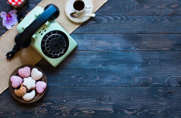 Vecchio telefono vintage, con biscotti, caffè, ciambelle su uno sfondo di legno