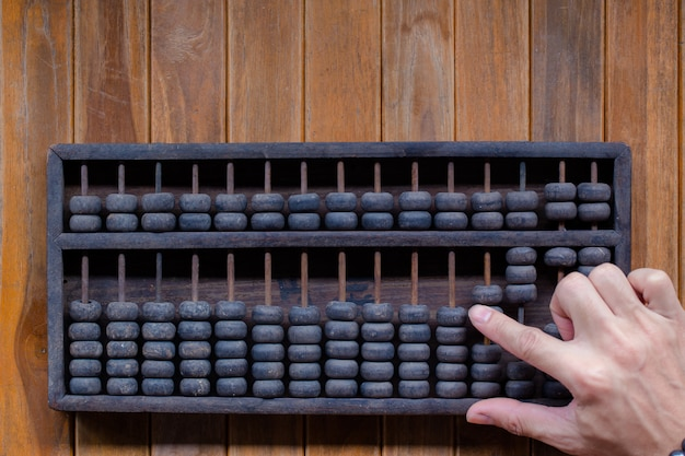 Il vecchio tono d'annata delle mani dell'uomo contabilità con il vecchio abaco e tiene il calcolatore elettronico. disegno di concetto finanziario dell'immagine.