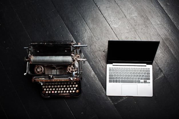 Vecchia macchina da scrivere vintage e computer portatile moderno