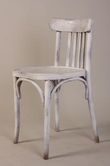 Vecchia sedia di legno bianca d'annata isolata su bianco