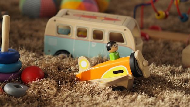 Vecchi giocattoli in legno vintage per neonati o bambini su un tappeto di colore marrone chiaro che ha una palla per autobus aeroplano