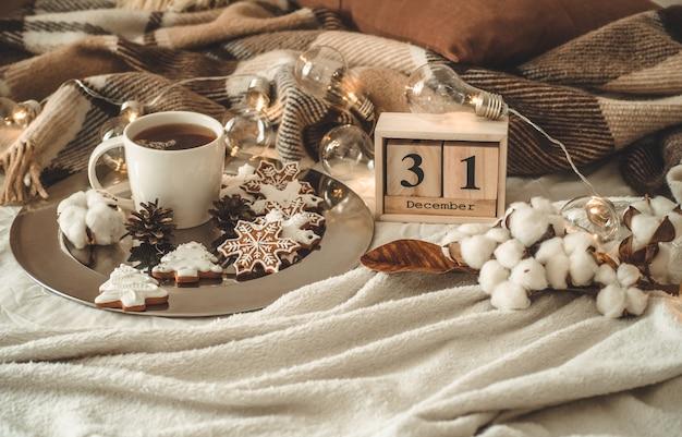 Vecchio calendario in legno vintage impostato il 31 dicembre con una tazza di tè.