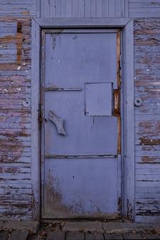 Vecchia porta chiusa in legno vintage, viola con vernice scrostata