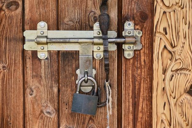 Vecchia porta di legno dell'annata con un lucchetto