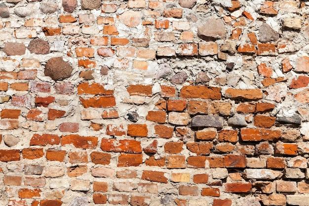 Vecchio muro, costruito con mattoni rossi.