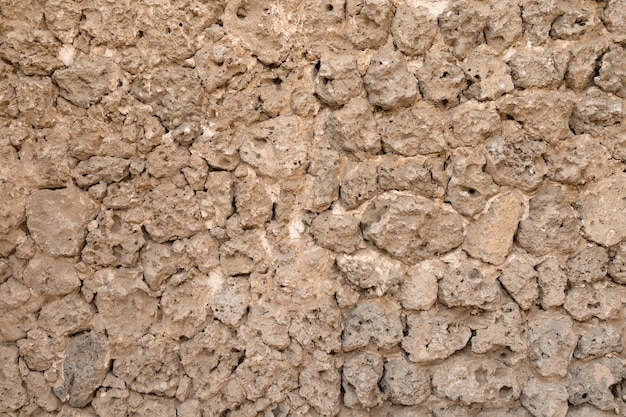Un vecchio muro fatto di pietre e argilla. muro strutturato per lo sfondo