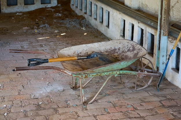 Vecchia carriola, pala e rastrello in un capannone