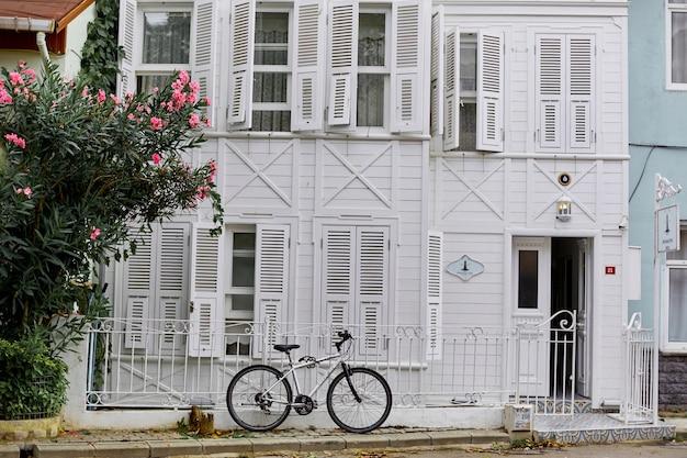 Un vecchio edificio bianco con una bici parcheggiata. strade dell'isola di buyukada.
