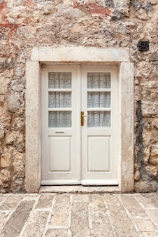 Vecchia porta classica bianca in antico edificio in pietra